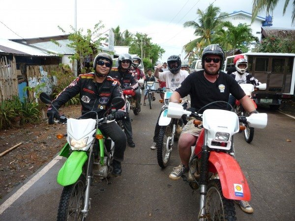 Charley Boorman and a group of local bikers on set filming Freedom Riders Asia in Puerto Princesa Philippines
