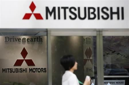 A woman walks in front of Mitsubishi Motors Corp's headquarters in Tokyo