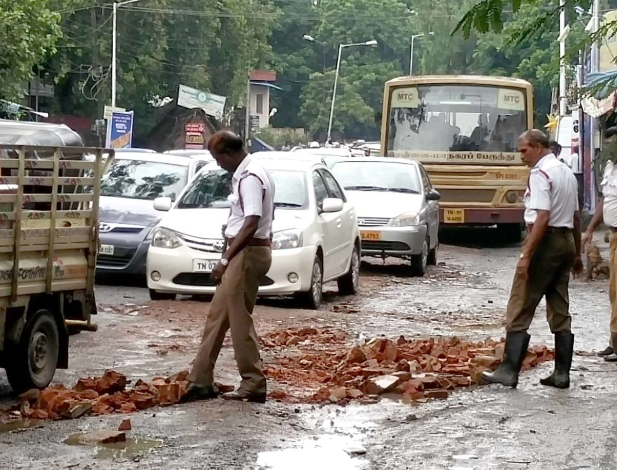 Policemen fill potholes with bricks in a rain lashed Chennai (6)