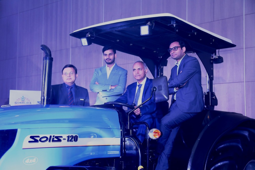 Mr. Deepak Mittal in middle sitting on 120 Hp tractor, Mr. Raman Mittal on extreme Left with Mr. Rahul Mittal on right of deepak Mittal with Gaurav Saxena on extreme right